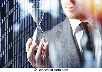 uomo affari, presa a terra, uno, hourglass., concetto, di, scadenza, in, affari