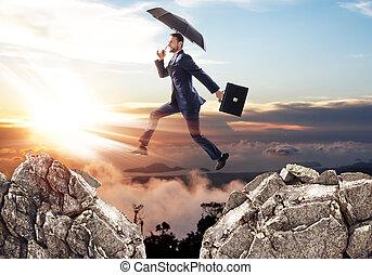 uomo affari, saltando, uno, scogliera, con, umbrella.