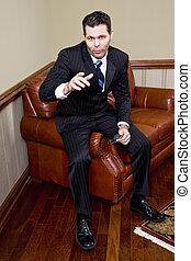 uomo affari, sedendo divano, indicando, macchina fotografica