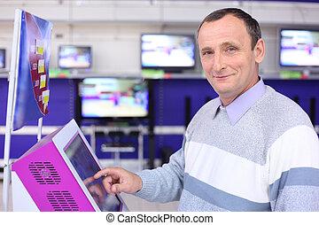 uomo anziano, in, negozio, a, informazioni, schermo