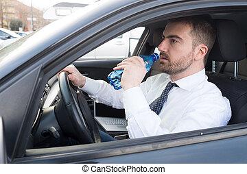 uomo beve acqua, seduto, automobile