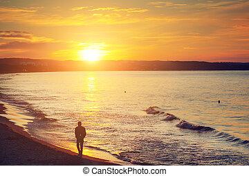 uomo cammina, solo, spiaggia, a, sunset., calma, mare
