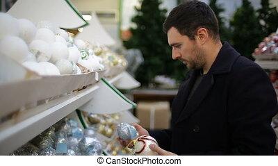 uomo, chooses, decorazioni natale, in, uno, negozio