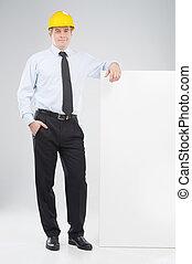 uomo, in, hardhat., allegro, mezza età, uomo, in, formalwear, e, hardhat, standing, appresso, manifesto, e, sorridente