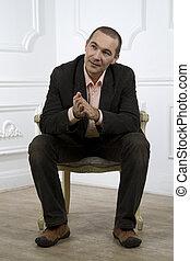 uomo, in, uno, completo, sedendo sedia