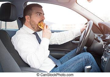 uomo, mangiare, un, hamburger, e, guida, seduto, automobile