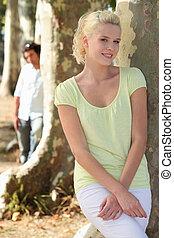 uomo, osservare, donna, inclinandosi, tronco albero