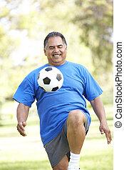 uomo senior, esercitarsi, con, football, parco