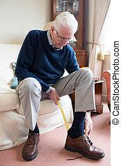 uomo senior, usando, lungo, handled, scarpa, corno, mettere, su, scarpe