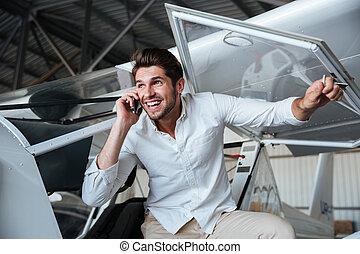 uomo sorridente, comunicando telefono, in, piccolo, aereo