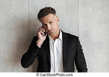 uomo sorridente, vestito, in, completo, comunicando telefono mobile