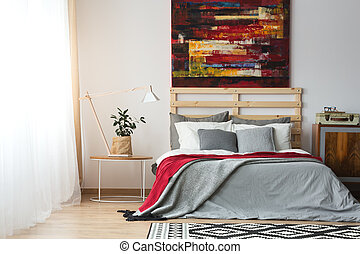 Up-to-date decor of spacious bright bedroom with poster and bed