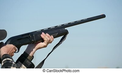 Up- to-date shortgun aims and shoots on a skeet range in...