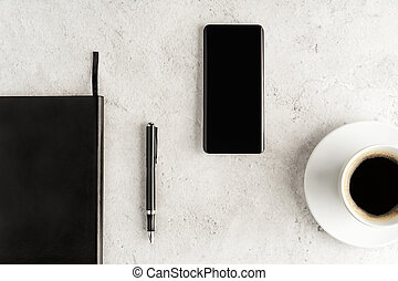 Up-to-date smartphone with notebook, fountain pen and cup of coffee on concrete background. Workstation concept flat lay. Coffee break top view.