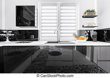 Up-to-date decor of stylish kitchen with shining black and white units