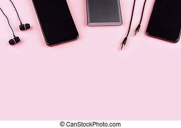 Up to date technology. Top view of diverse personal accessory laying on the pink background