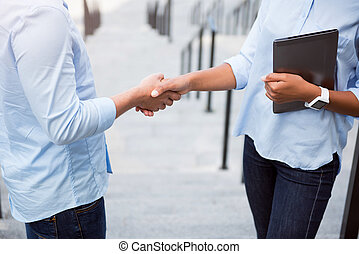 Verbal agreement. Cropped image of two business people shaking hands while holding a digital tablet