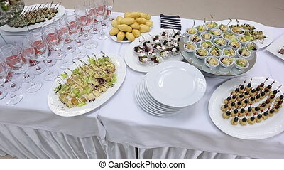 Up view of banquet table with appetizers, canapes, plates and glasses.