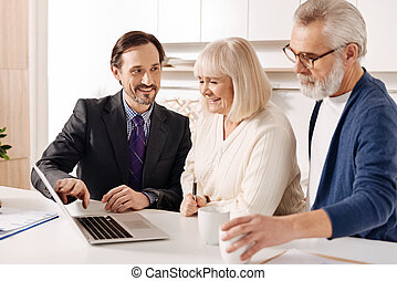 Upbeat agent presenting plan of the house to future owners