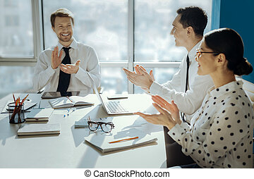 Upbeat colleagues clapping hands during meeting in office