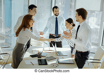 Upbeat colleagues greeting each other before business meeting