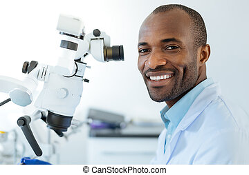 Upbeat dentist posing while using microscope