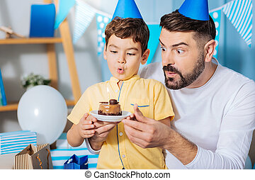 Upbeat father and son blowing out candle on birthday cake -...