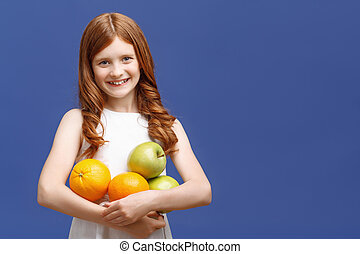 Upbeat girl holding fruits - Real emotions. Vivacious young ...