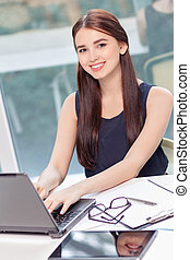 Upbeat girl sitting with laptop