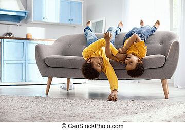 Upbeat little brothers lying on the couch and tickling each other