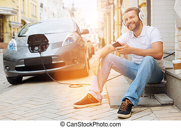Upbeat man listening to the music on the steps