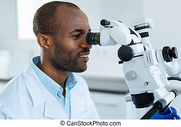 Upbeat man studying oral cavity with help of microscope
