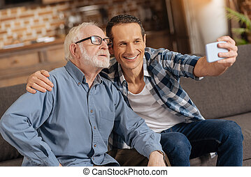 Upbeat man taking a selfie with his elderly father