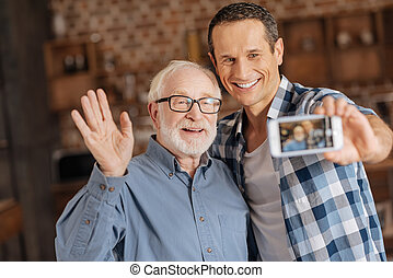 Upbeat man taking pictures with his senior father