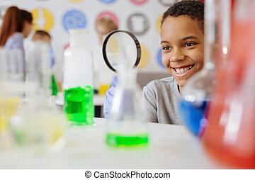 Upbeat schoolboy smiling while checking content of chemical flask