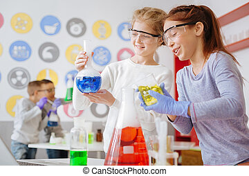 Upbeat schoolgirls checking for the desired chemical reaction in flask