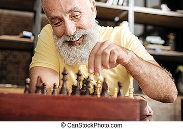 Upbeat senior man playing chess at home