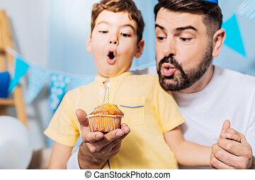Upbeat son and father blowing out candle on muffin
