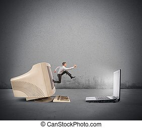 Upgrade - Businessman jumping from old computer to new...