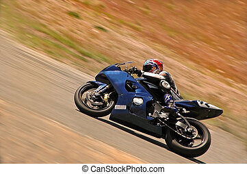 A motorcycle racer speeds up hill