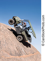 Uphill Climb - Offroad vehicle climbing up a sheer cliff and...