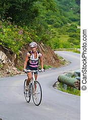 Uphill on a bicycle - Young girl on a bicycle moving up to a...