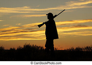 an upland game hunter silhouetted with shotgun in a colorful sunset