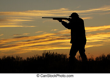 an upland game hunter with gun up to shoulder in the sunset