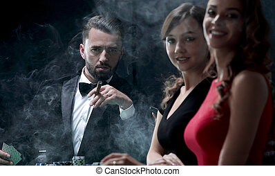 Upper class friends gambling in a casino. - four people...