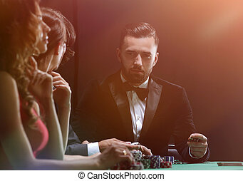 Upper class friends gambling in a casino - Losers and...
