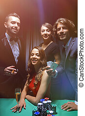 Upper class friends gambling in a casino. - Young people...