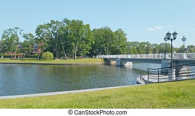 Pedestrian bridge on quay of Upper Lake - artificial city pond, famous tourist sight and popular leisure zone in Kaliningrad, Russia at sunny summer day. Static shot rendered in 4K