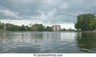 View from embankment of Upper Lake - artificial city pond, famous tourist attraction and popular recreation zone in Kaliningrad, Russia at springtime on cloudy day. Static shot rendered in 4K