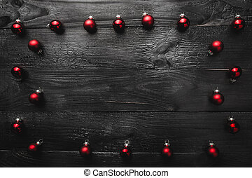 Upper, top, view from above, of evergreen red toys on black wooden background, with space for text writing, greeting.